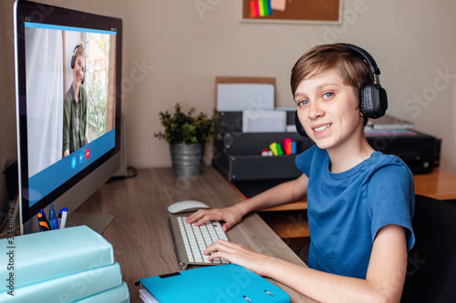 A teenage boy communicates with relatives via a web camera video conference on the computer at home Canvas Print