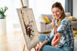 canvas print picture - Beautiful woman painting on canvas at her home or workshop