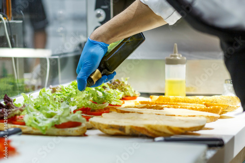 Obraz na plátne Banconista prepara dei panini assortiti aggiungendo dell'olio