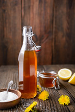 Homemade Healthy Dandelion Syrup In A Glass Bottle, Decorated With Fresh Flowers With Copy Space
