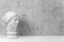 Mockup With Ancient White Statue Of Bust Of Venus With Grey Textured Background .Plaster Sculpture Woman Face. The Goddess Of Love In Greek Mythology. Renaissance Epoch. Copy Space.