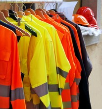 High Visibility Jackets On A Hanger With Protective Helmets Behind, In A Work Clothes Store .