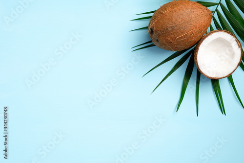 Leinwand Poster Summer background with tropical palm leaf and coconut fruit on blue background