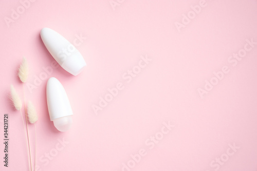 Antiperspirant deodorant bottles and dry flowers on pink background Canvas Print