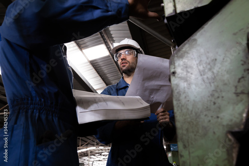Factory engineer reading manual of machine operation and standing with blue working suite dress and safety helmet Canvas Print