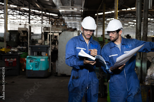 Fotografía Factory engineer reading manual of machine operation and standing with blue working suite dress and safety helmet