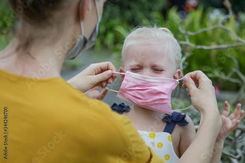 Mummy struggles to put medical mask on her child's face Принти на полотні