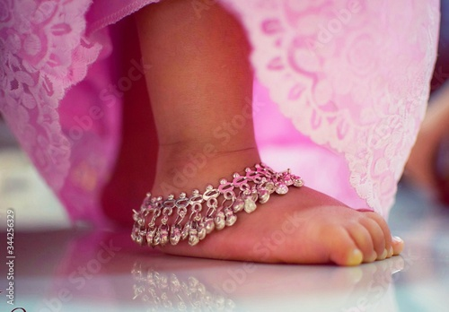 Low Section Of Girl Wearing Anklet On Floor Canvas Print