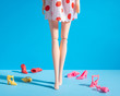 canvas print picture - Doll legs with different shoes on a blue background. Minimal fashion composition.