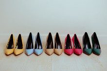 Multiple Pairs Of Kitten, Stiletto High Heels Of Different Colors. Woman Classic Dress Shoes Aligned On A Floor.