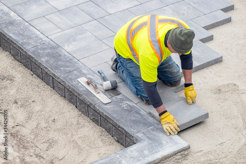 Fototapety, obrazy: Workman in Safety Jacket Laying Patio Pavers in a Backyard