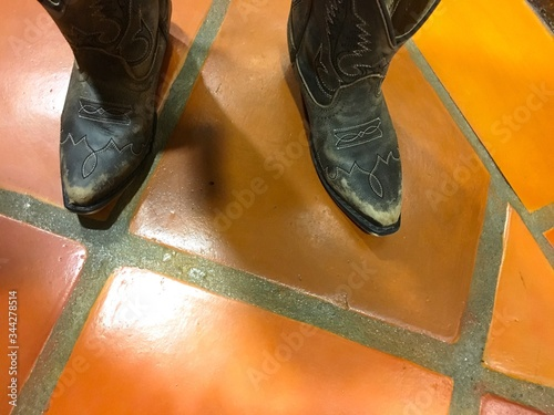 Valokuvatapetti Low Section Of Person Wearing Cowboy Boots On Orange Tiled Floor