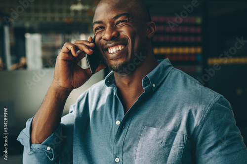 Leinwand Poster Businessman talking over mobile phone in office