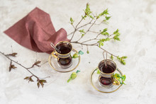 Glass Cups With Fruit Tea, Napkin And Spring Tender Tree Branches On Light Background, Top View