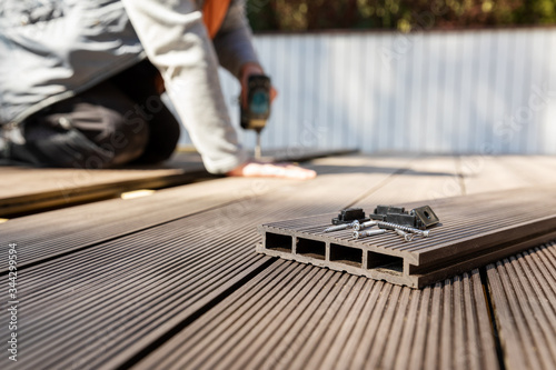 Fototapeta wpc terrace construction - worker installing wood plastic composite decking boards obraz na płótnie