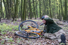 Fall From Bike In Natural Park. Young Caucasian Man Fell Off The Bicycle On The Ground. Accident With A Stick In A Wheel. Outdoors