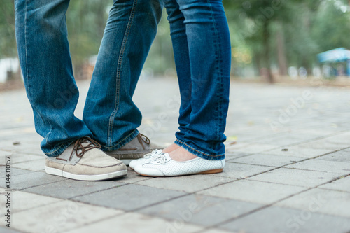 two pairs of feet of a romantic couple on a sidewalk tile Canvas Print
