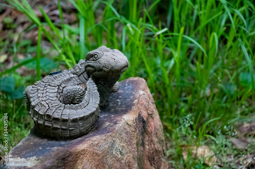 A lifelike alligator water sprinkler perches on a rock in a rustic garden against a background of tall grass Canvas Print