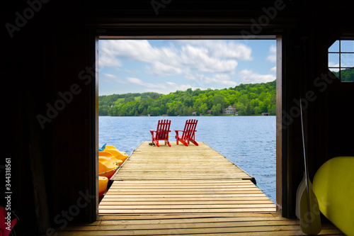 Billede på lærred View of two red Adirondack chair on a wooden dock from a cottage's boathouse in Muskoka, Ontario Canada