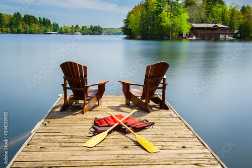 Fototapeta Two Adirondack chairs on a wooden dock facing the blue water of a lake in Muskoka, Ontario Canada
