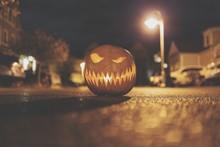 Close-up Of Illuminated Jack O Lantern On Road At Night