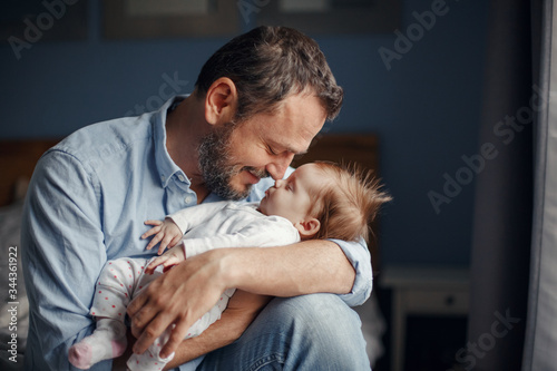 Obraz Middle age Caucasian father kissing sleeping newborn baby girl. Parent holding rocking child daughter son in hands. Authentic lifestyle parenting fatherhood moments. Single dad family home life. - fototapety do salonu