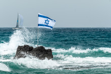 Scenic View Of Rock With Flag In Sea Against Clear Sky