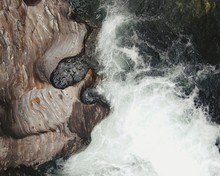 High Angle View Of Waves Splashing On Rock Formations At Beach