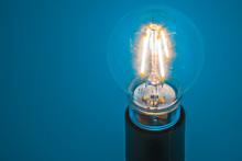 Close-up Of Illuminated Light Bulb Against Blue Background