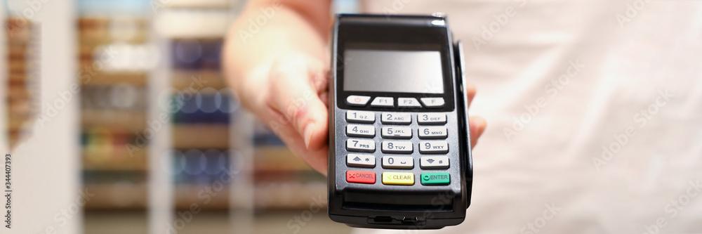 Fototapeta Male businessman hand hold POS terminal closeup. Fast digital payment concept