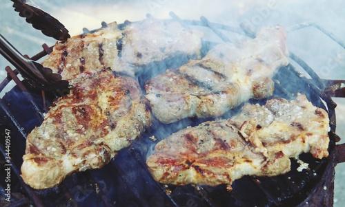 Fotografía Asando chuletones de cerdo ibérico en una barbacoa con carbón vegetal