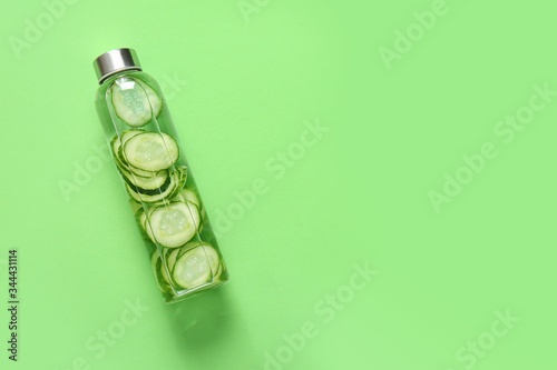 Fotomural Bottle of cucumber infused water on color background
