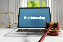 Blockbusting – Law, Judgment, Web. Laptop In The Office With Term On The Screen. Hammer, Libra, Lawyer.