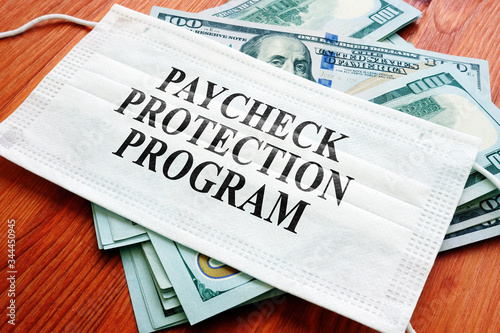 Foto PPP Paycheck Protection Program as SBA loan written on the mask and money
