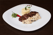 Filet Mignon With  Creamy Mushroom Sauce And Mashed Potatoes On White Plate. Restaurant Dish Decorated With Red Chili Pepper And  Microgreen. Dark Background