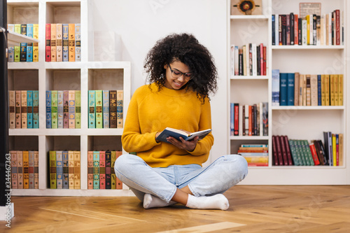 Fotomural Image of joyful african american woman reading book while sitting