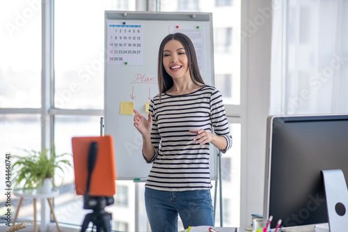 Dark-haired girl in a striped shirt recording a video Fototapet