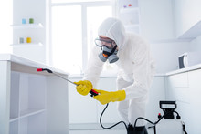 Profile Side Photo Of Focused Cleaner Coverall Worker Guy Hold Sprayer Spray Table Shelves Use Protective Equipment Prevent Covid Spreading In Kitchen House Indoors