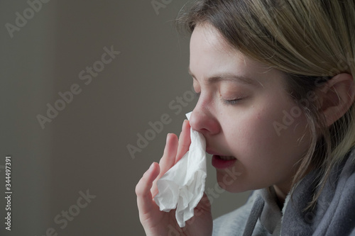 Fototapeta Sick woman with runny nose sitting under the blanket.