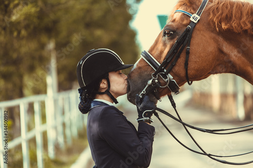 Young teenage girl equestrian kissing her favorite red horse Wallpaper Mural
