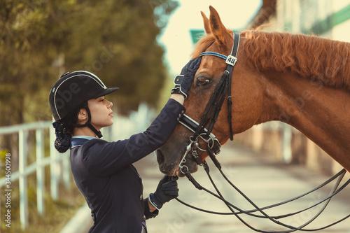 Fotografie, Obraz horsewoman jockey in uniform standing with black horse outdoors