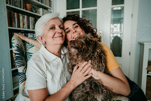 .Adorable portrait of a mother and daughter accompanied by their dog while at ho Canvas Print