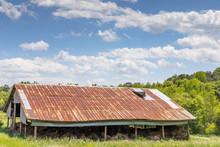 View Of A Field, Pole Barn With Rusty Tin Roof, Open Sides With Hay Bales, Idyllic Blue Sky With Clouds, Copy Space, Horizontal Aspect