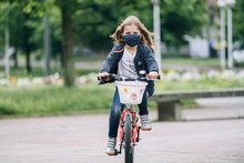 Little Girl Riding A Bike With...