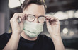 young attractive man with blue eyes and glasses puts on a respirator mask with fogged glasses