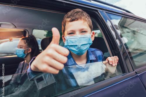 Fototapeta Kids wearing anti virus masks and using digital tablets in the car. Kids are travelling in car during coronavirus outbreak obraz