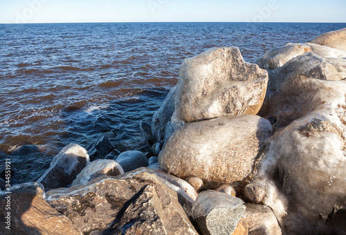 Fotografija Huge boulders covered with ice against the blue water of Lake Ladoga on a sunny