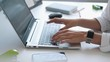 Business woman using a laptop computer at a desk, female hands typing on a keyboard. Close-up
