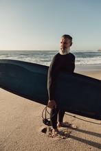 Smiling Senior Man Carrying Surfboard At Beach