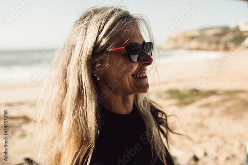 Smiling senior woman wearing sunglasses standing on beach - 344572161